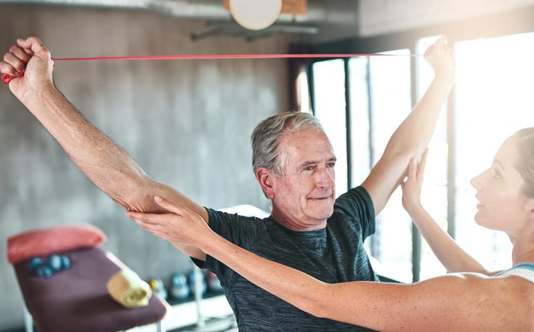 elderly man stretching with resistance band