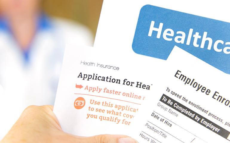 Image of hand holding several generic health benefit forms.