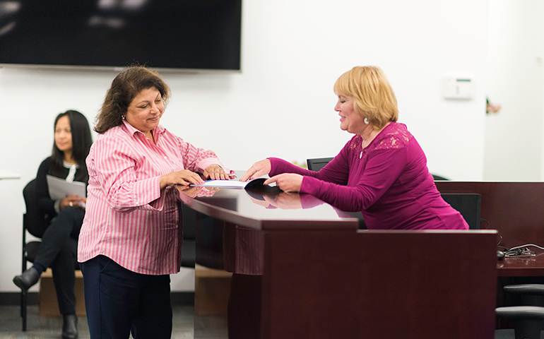 Image of an SFHSS Benefits Analyst assisting another SFHSS member in the SFHSS lobby.