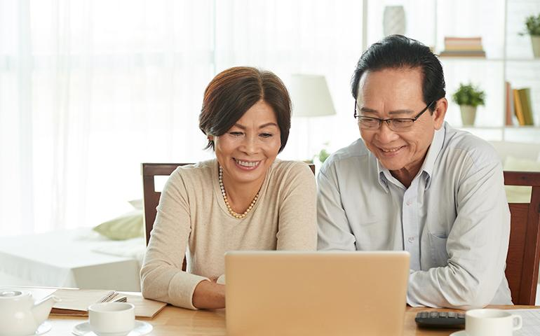 Older Asian couple sitting at home in front of a laptop.