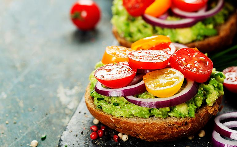 Image of a healthy veggie sandwich with cut red and yellow tomatoes, avocado and sliced red onions.