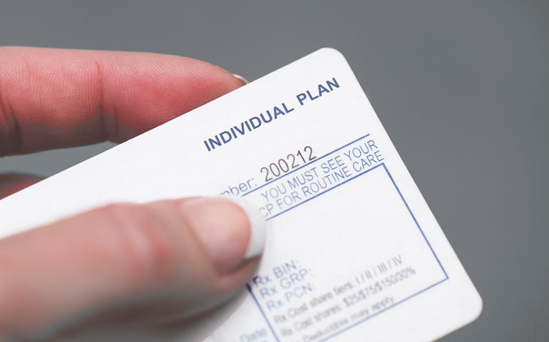 "Image of a hand holding a generic insurance ID card that says ""Individual Plan"""
