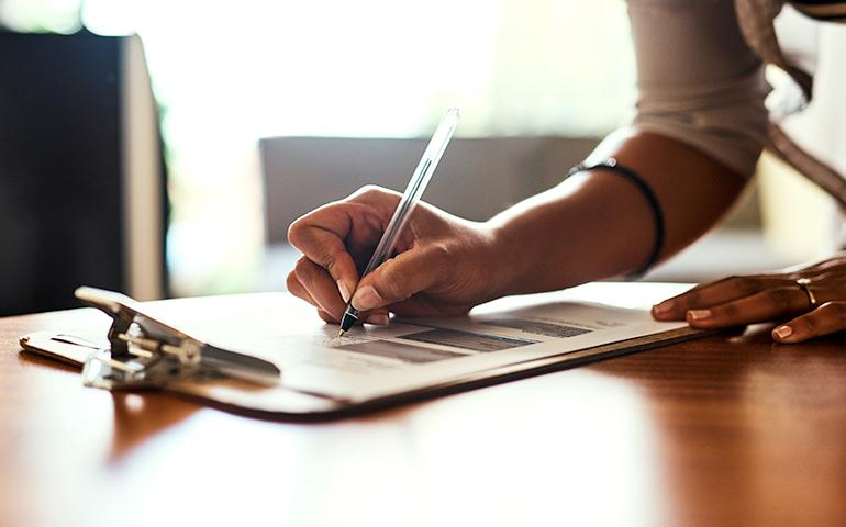 Photo of woman's hand leaning down and writing on a clip board.