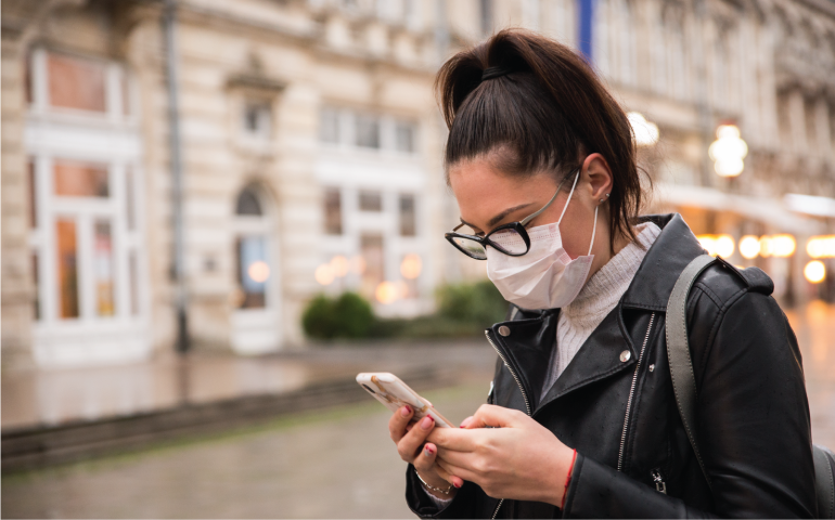 Woman Wearing Mask Looking at phone