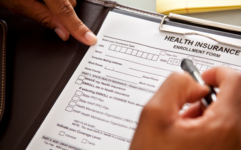 Image of person filling out a health plan enrollment form.