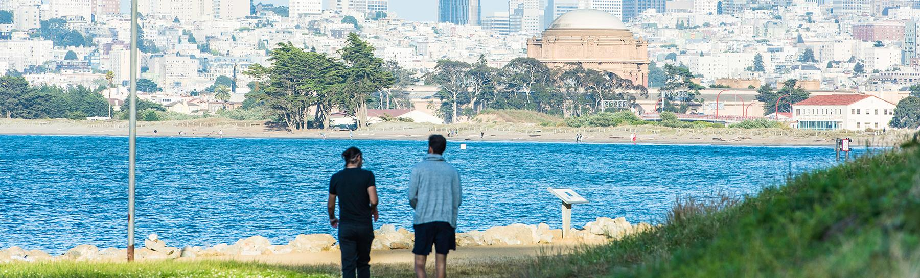 Photo of two people walking along the path that is along the San Francisco Bay near Fort Mason with a view of the City skyline ahead of them.