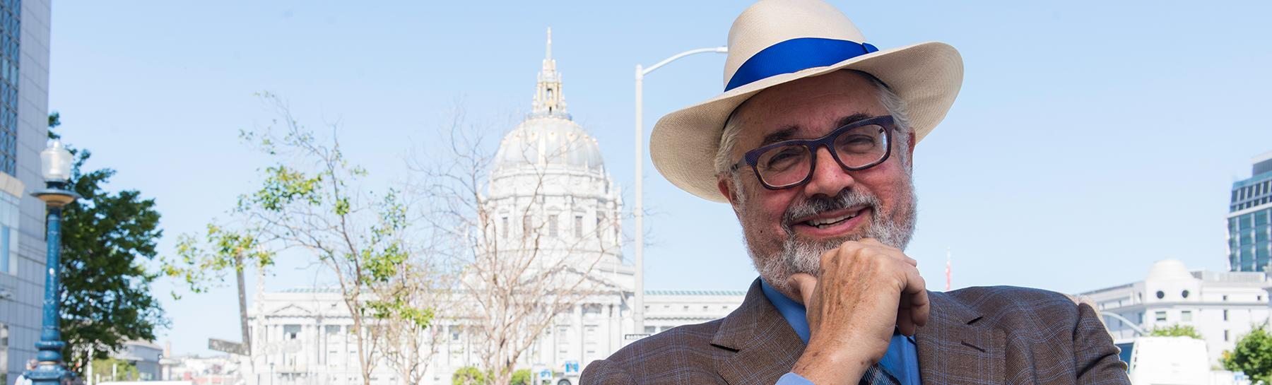 Image of a City and County of San Francisco retiree wearing a hat and standing in the Civic Center with City Hall in the distance.