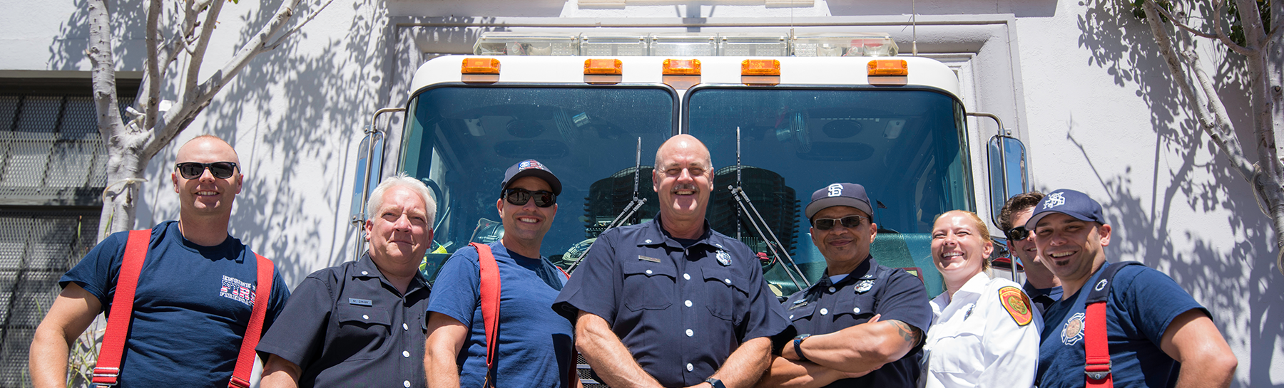 Image of a group of City and County of San Francisco firefighters posing together in front of a fire truck along the Embarcadero in San Francisco.