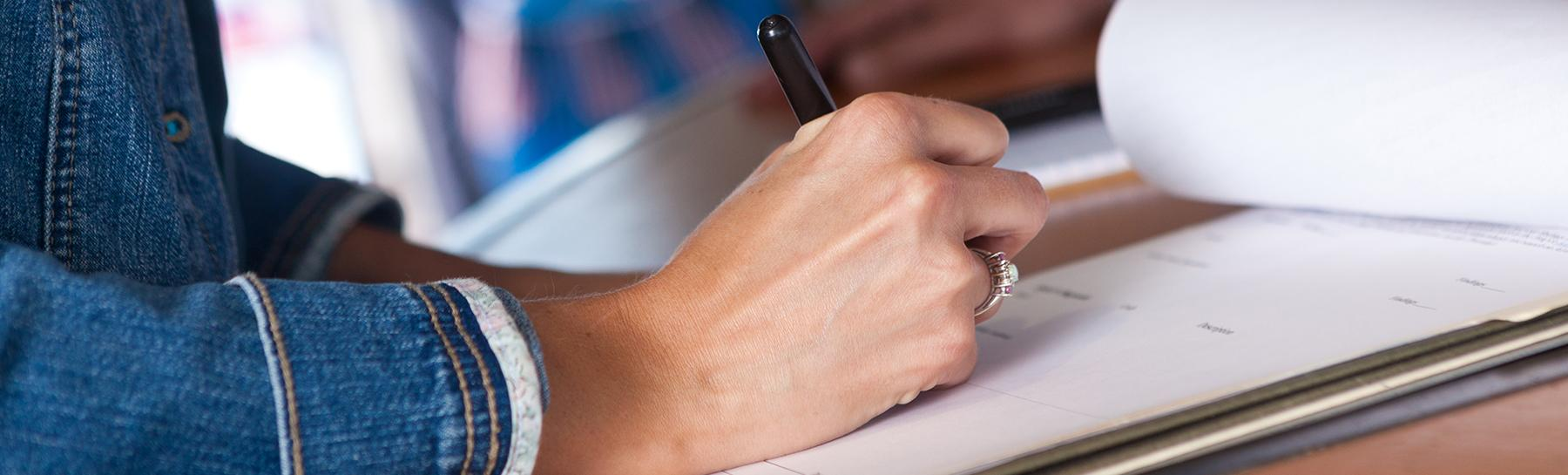 Image of hand writing on a notepad.