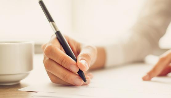 Photo of a woman's hand writing on a pad with a black pen.